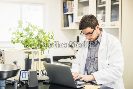 scientist typing on laptop in laboratory