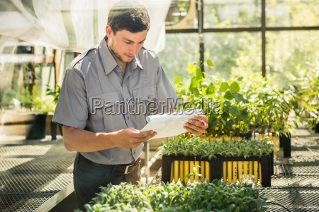 scientist reading paperwork in plant growth