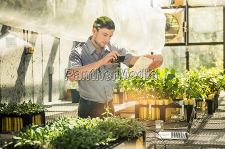 scientist photographing paperwork in plant growth