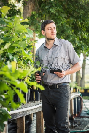 scientist using digital tablet at plant