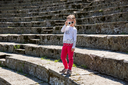 girl photographing from stone stairway at