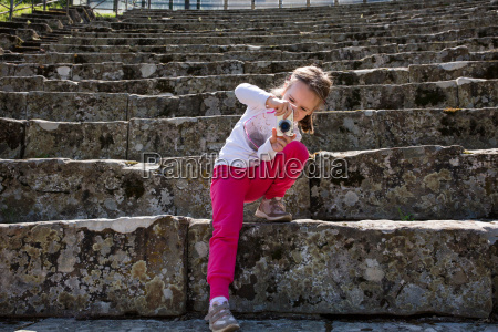 girl photographing stone stairway at ruins