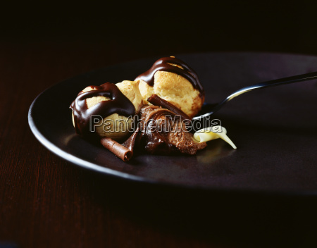 chocolate covered profiteroles with spoon on