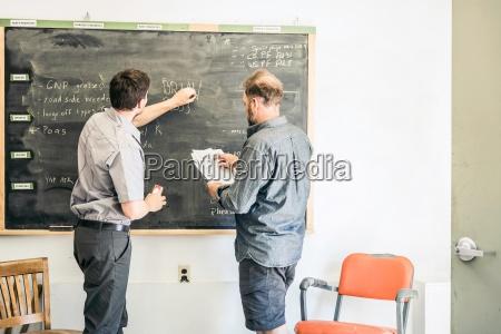 scientists chalking on blackboard in plant