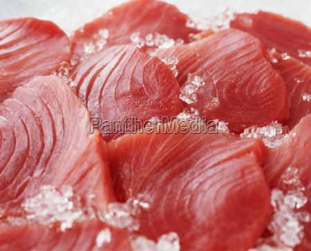 raw sliced tuna steaks on crushed