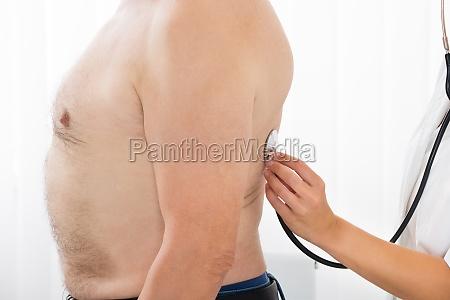 arzt hand untersuchen ruecken des patienten