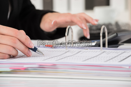 businesswoman hand calculating business report