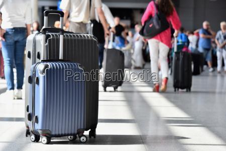 zwei kunststoff reisekoffer in der flughafenhalle