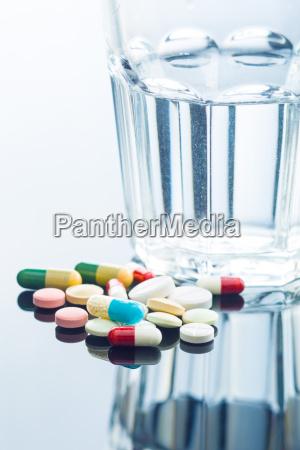 die verschiedenen pillen und ein glas