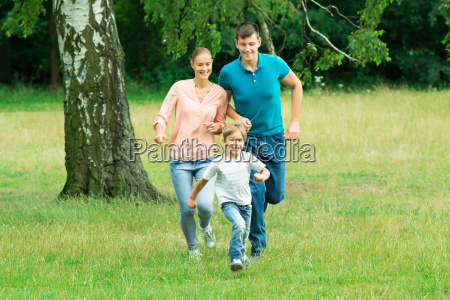 boy running ahead of his parent