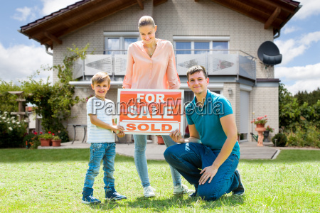 family with a sale sign outside