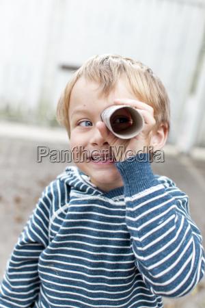 kleiner junge mit fernglas