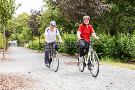 smiling senior couple cycling in park