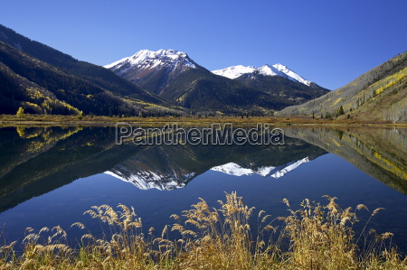 snow capped red mountain reflected in