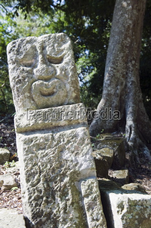 sculpted head stone at mayan archeological