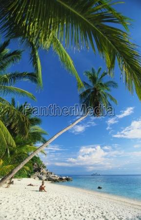 drei personen sonnenbaden am strand von
