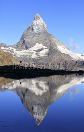 hiker admiring the matterhorn reflected in