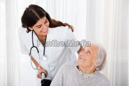 female doctor helping handicapped senior patient