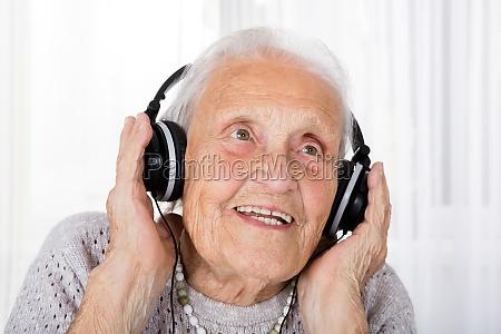 senior woman using headphone at home