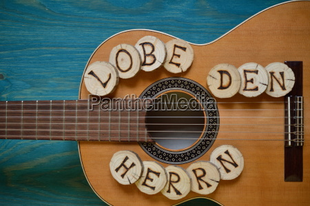 gitarre auf blaugruenem holz mit worte
