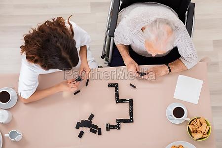 elder frau spielen domino spiel mit