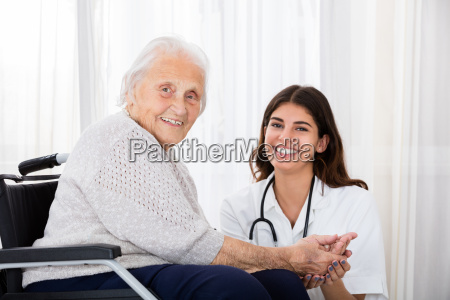 female doctor with disabled senior patient