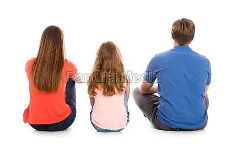 family sitting on white background