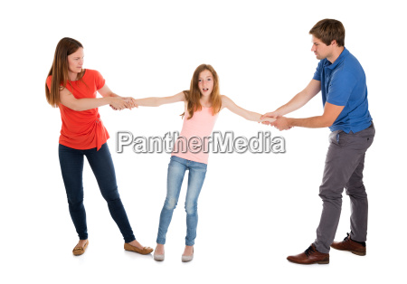 unhappy couple pulling their daughter on