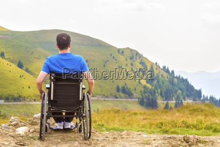 optimistic handicapped man sitting on wheelchair