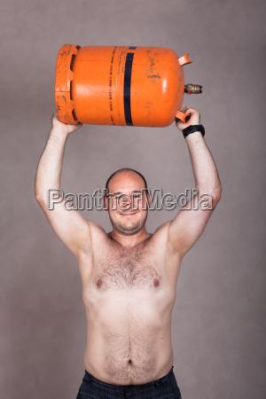 starker hemdsliger mann der eine gasflasche
