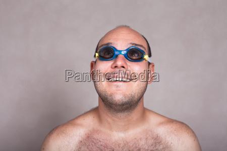 lustiger mann in schwimmbrille tagtraeumen und