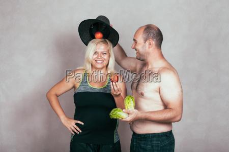 froehliches korpulentes paar mit obst und
