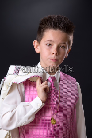 young boy holding his jacket over