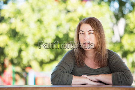 pretty woman seated at table outside