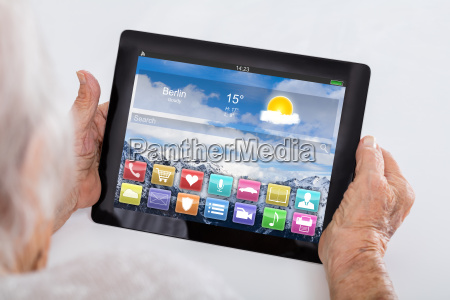 senior woman holding digital tablet showing