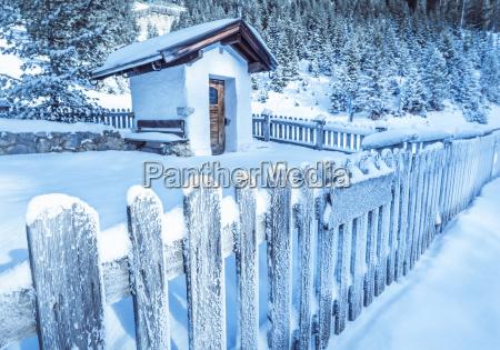 gefrorener holzzaun und rustikale kapelle