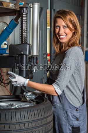 weibliche mechaniker wechselnden autoreifen