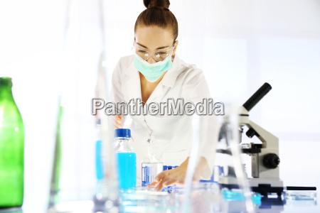 chemist examine the sample under a