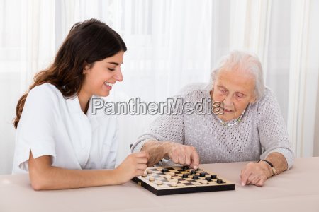 zwei frauen die checkers spiel spielen