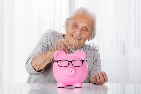 senior woman inserting coin in piggybank