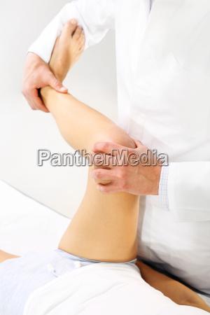 orthopedic doctor physiotherapist examining patients leg