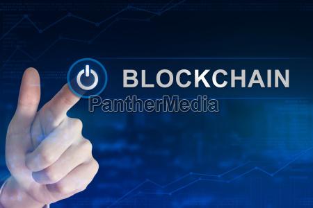 business hand clicking blockchain button