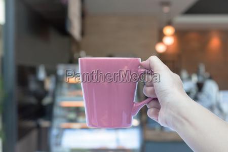 frau haende halten kaffeetasse mit verschwommenen