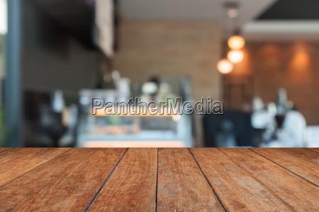 perspektivbraunes holz mit verschwommenem cafe