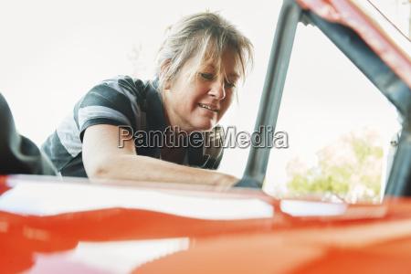 mature woman repairing a car looking