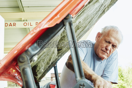 senior man repairing a car looking