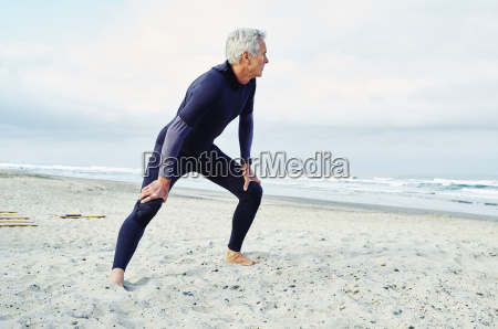senior man wearing wetsuit standing on