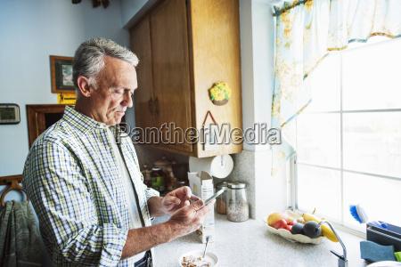 senior man standing in a kitchen