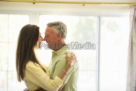 senior couple standing indoors embracing