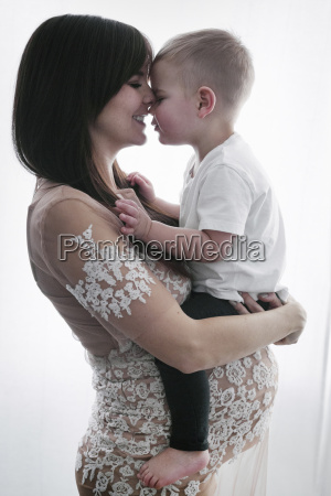 a pregnant woman holding her young